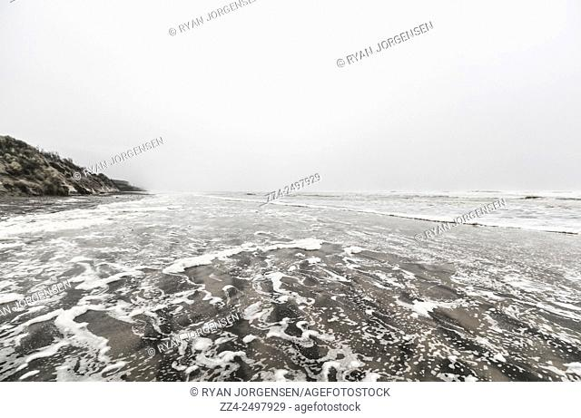 White ocean wash and rain flood the shores of a turbulent coastline during rough winter climate. Ocean Beach, Tasmania, Australia