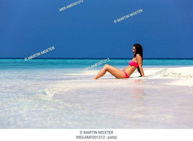 Maldives, Young woman in bikini sitting in shallow water