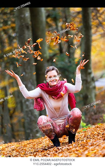 Teenager is playful with Autumn leaves
