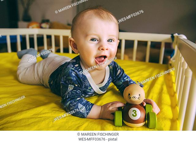 Portrait of baby boy with wooden toy lying in his crib