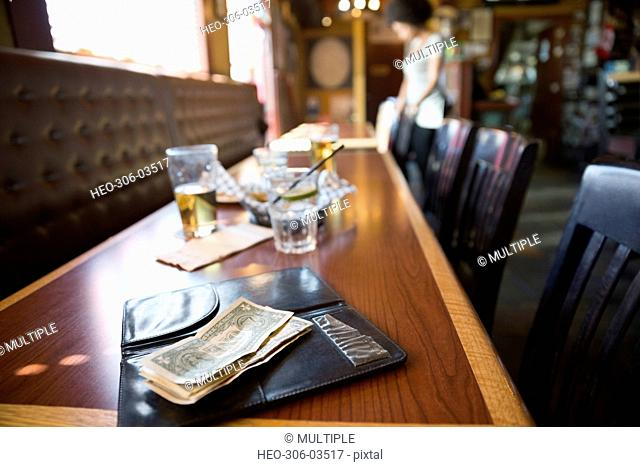 Cash tip on table in bar