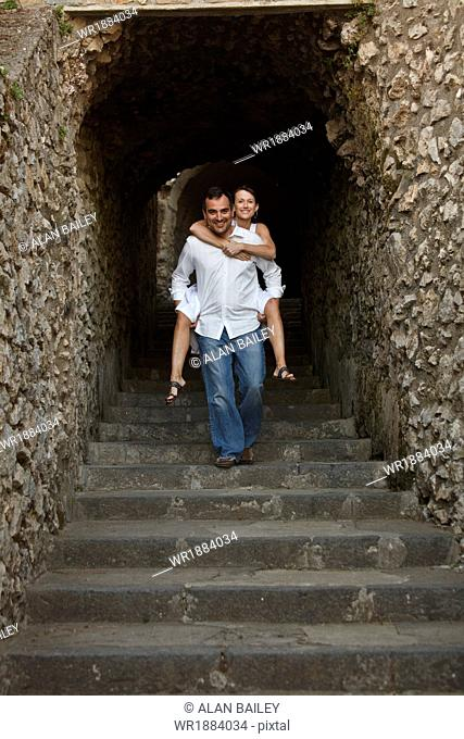 Italy, Ravello, Mature woman piggyback riding on man in stone archway