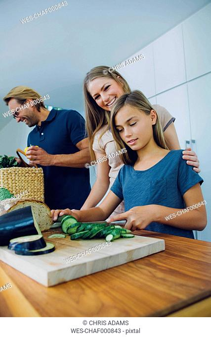 Mother and daughter in kitchen slicing cucumber with father in background