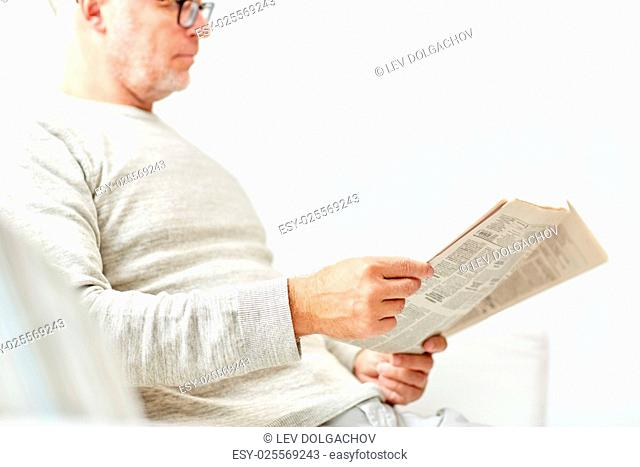 information, people and mass media concept - close up of senior man reading newspaper
