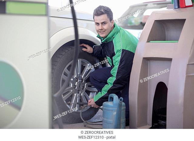 Man filling car tyres with air at fuel station