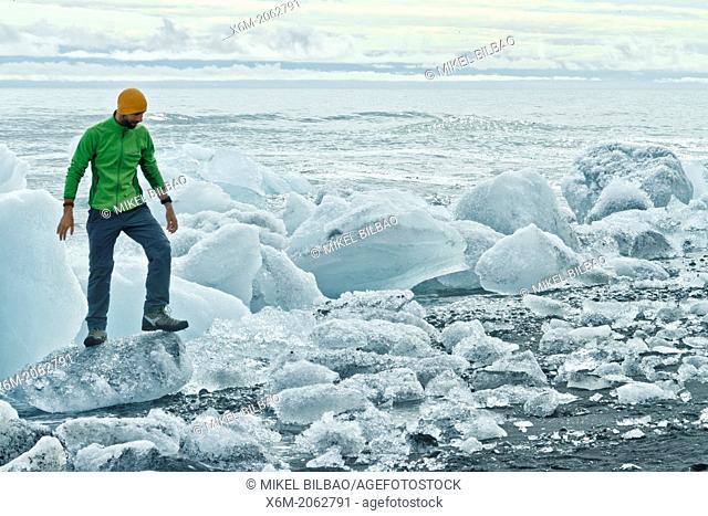 People and ice blocks in Jokulsarlon sand beach. Vatnajokull National Park. Iceland, Europe