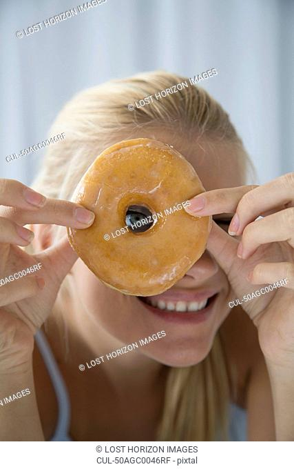 Woman peering through donut hole