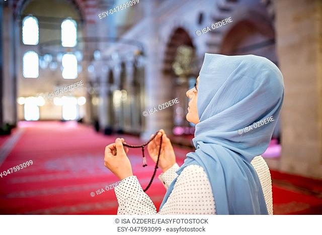 Muslim woman in headscarf and hijab prays with her hands up in air while holding rosary in mosque. Religion praying concept