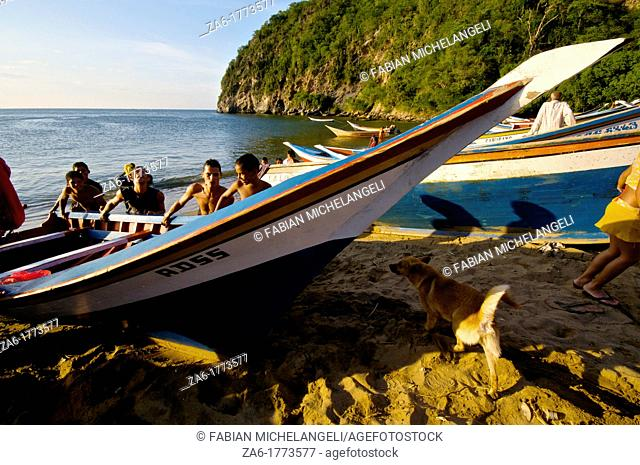 Pushing a fishermen's boat to the shore  Paria Peninsula, Eastern Venezuela