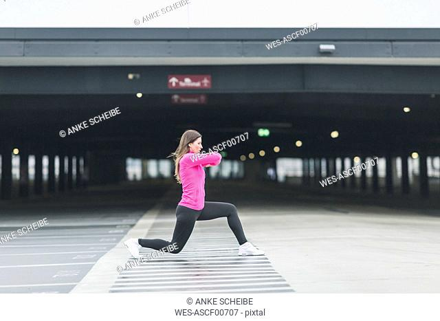 Woman stretching at parking garage