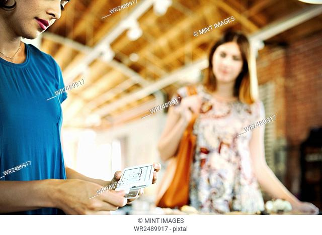 Two young women in a shop, using a credit card reader