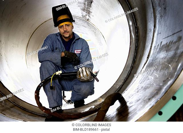 Hispanic male welder inside large metal pipe