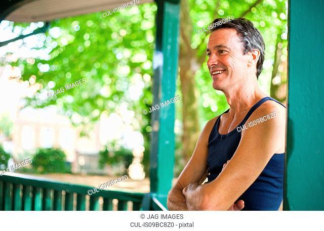 Mature man standing under bandstand, smiling