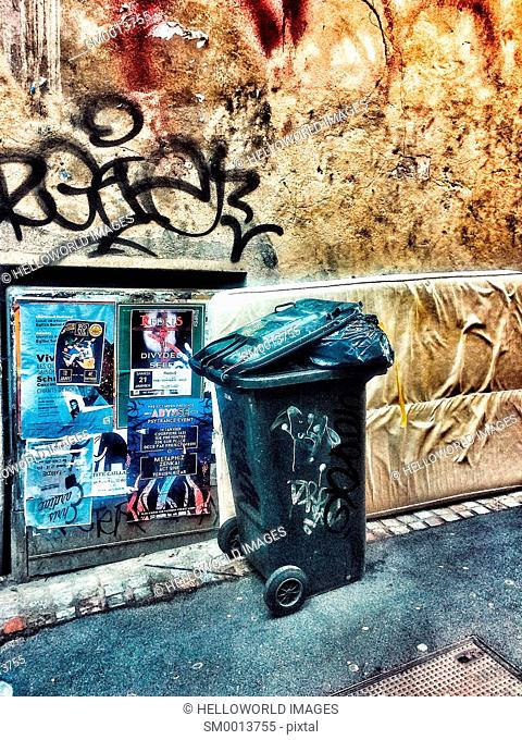 Overflowing rubbish bin, mattress and posters in street, France, Europe