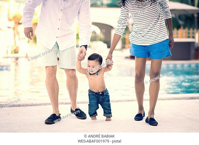 Mexico, Puerto Vallarta, baby boy learning to walk holding by hands of his parents