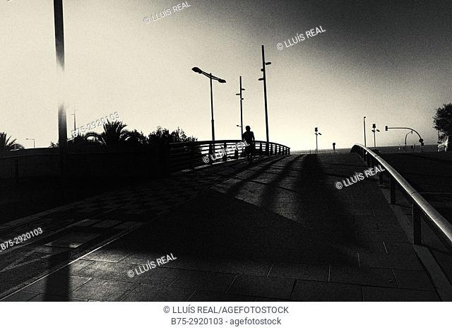 Silhouette of man walking on bridge. Diagonal Mar, Barcelona, Catalonia, Spain