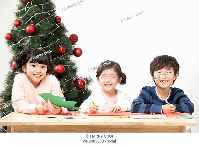 Portrait of three smiling children making paper Christmas tree staring at front