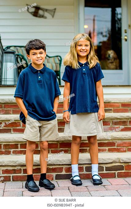 Portrait of male and female elementary school twins outside home porch
