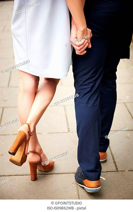 Cropped rear view of couple holding hands
