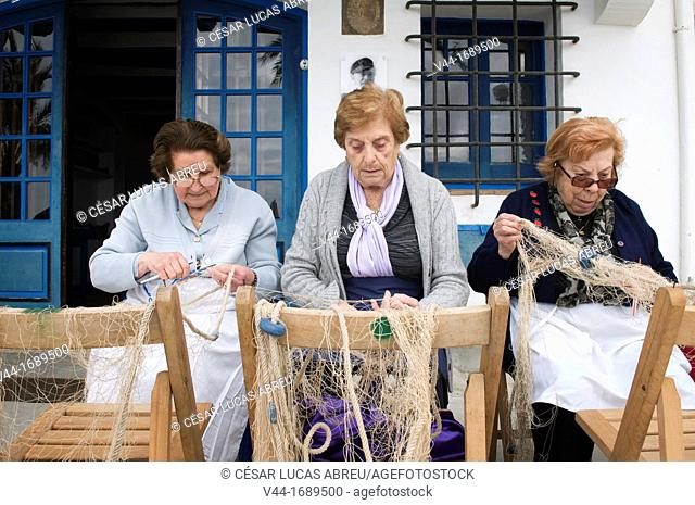 Old women mending fishing nets in front of the Museum Casa Barral. Calafell, Costa Daurada, Catalonia, Spain