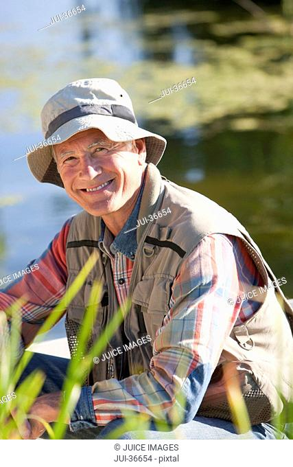 Portrait of smiling senior man at sunny lake