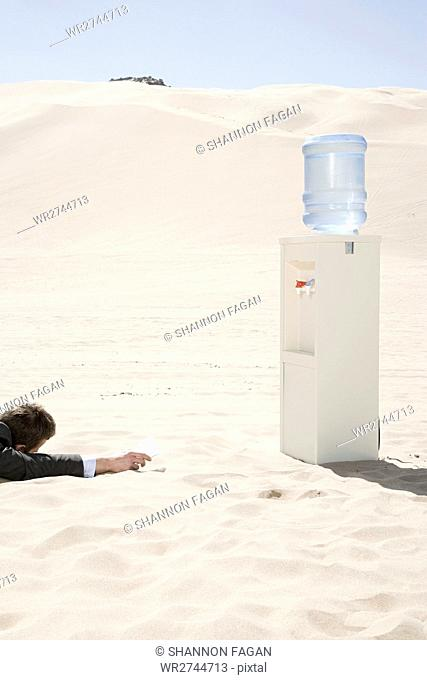 Man by water cooler in the desert