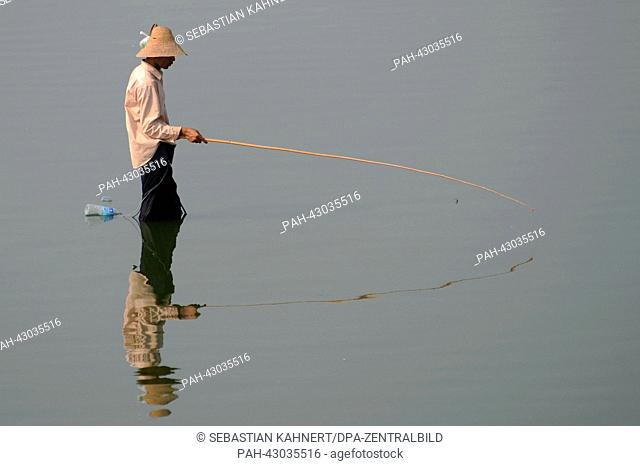 A fisherman is holds a fishing rod in his hands at the Taungthaman Lake in Amarapura, Myanmar, on 02 April 2013. Photo: Sebastian Kahnert | usage worldwide