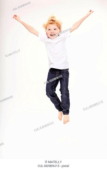 Portrait of boy leaping in air