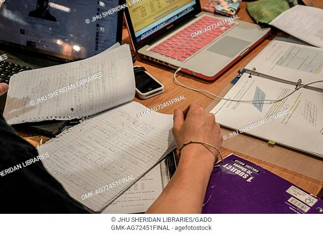 A close-view shot of a college student reviewing Calculus homework at a table, only their arm and hand visible, with another set of notes from a Calculus...