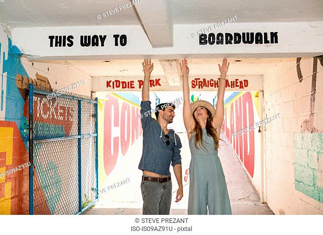 Couple in tunnel, arms raised reaching for sign, Coney island, Brooklyn, New York, USA