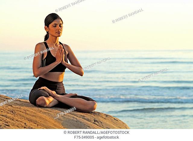 Indian girl meditating on beach in Carlsbad. California, USA