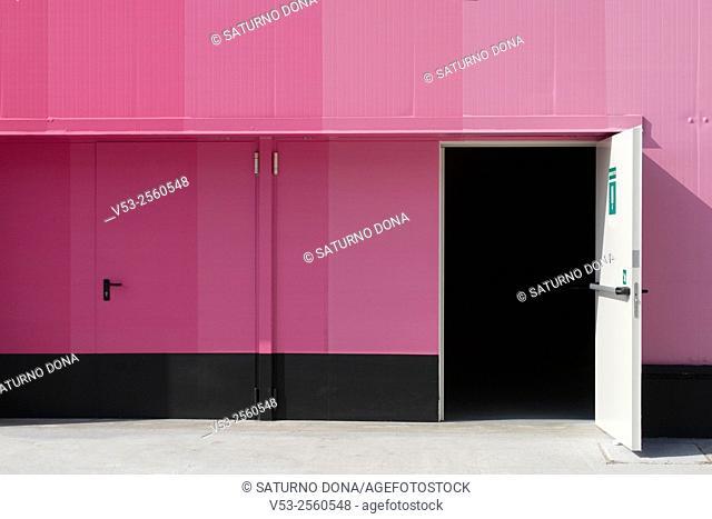 Pink industrial storage building with open door