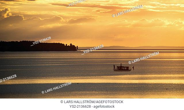 Tranquil summer night scene in Sweden. Silhouette of small steamboat on lake Vattern at sunset