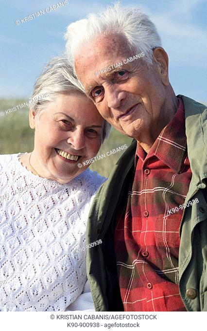 Waist up photograph of elderly caucasian couple looking into the camera, smiling and leaning to each other head to head with blue sky, Island of Amrum