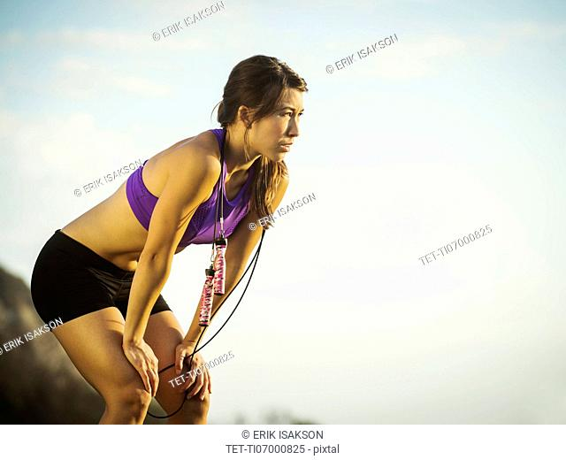 Young woman with jump rope resting