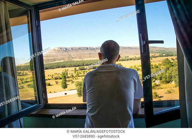 Man at a hotel window, looking at the landscape. Valonsadero, Soria, Spain