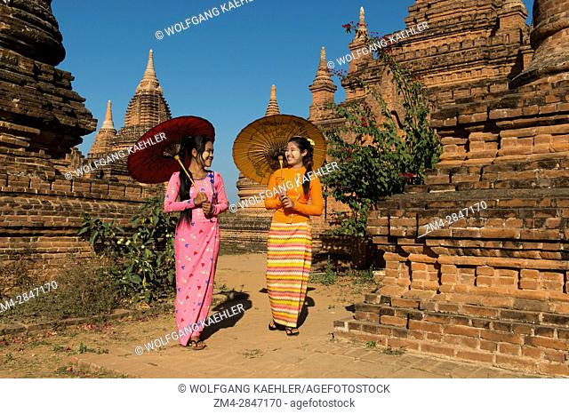 A model shoot with two young women in traditional dress and parasols at a small temple complex in Bagan, Myanmar