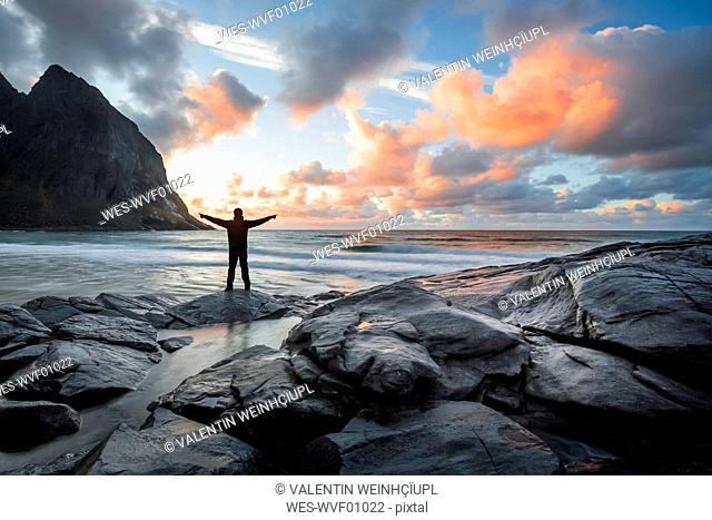 Norway, Lofoten Islands, man with raised arms at Kvalvika Beach in the evening