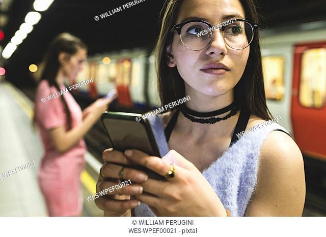 Teenage girl using cell phone at subway station