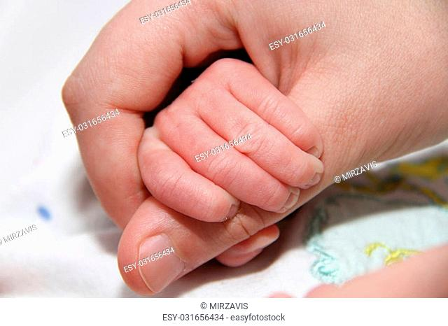 Photo of the Baby hand holding motherfinger, new born baby