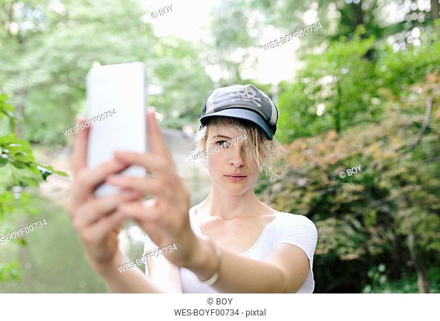 Young woman taking a selfie in park