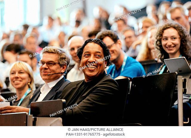 BAYREUTH/GERMANY - JUNE 21: Stefan Winners (Hubert Burda Media, m.) and Cherno Jobatey (Huffington Post) smile in the audience listening to the speaker during...