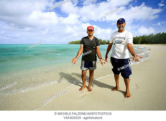 Local men with starfish, Ile aux Cerfs, Mauritius, Indian Ocean