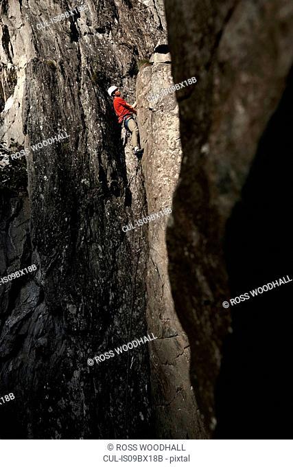 Rock climber scaling cliff face