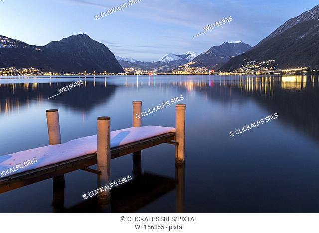 Evening lights of Lugano and Campione d'Italia in front of a pier on Lake Ceresio, Riva San Vitale, Canton Ticino, Switzerland