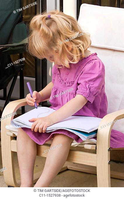 Young three year old girl drawing on paper with pen