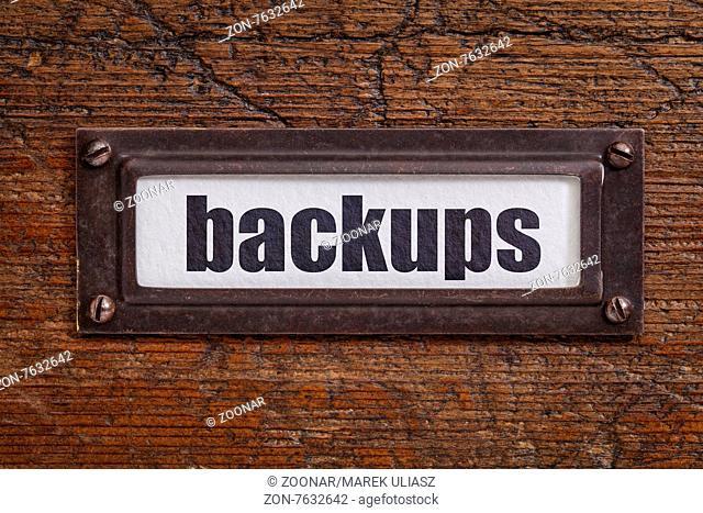 backups - a label on a grunge wooden file cabinet
