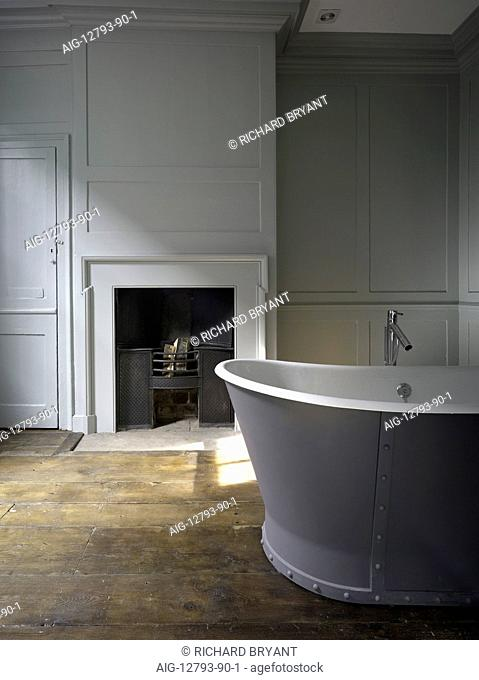 Georgian white panelled room with fireplace and large free-standing bathtub