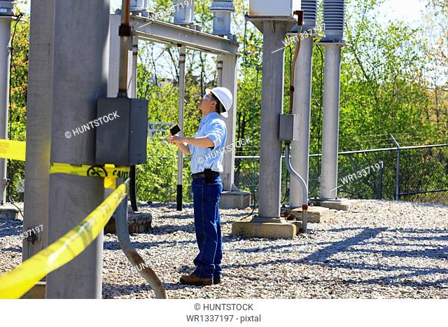 Power engineer using his cell phone at high voltage power distribution station, Braintree, Massachusetts, USA