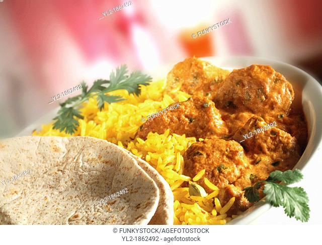 Chicken Tikka Masala - Pilau rice & naan bread in white dish with red background